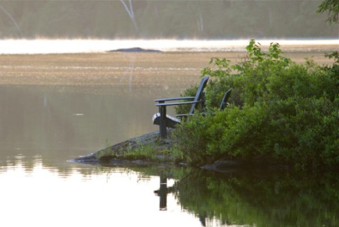 Watching an awakening day at Otter Lake, Ontario: June sunrise at a rocky point with traditional wood Muskoka chairs, listening to bird calls ... swatting mosquitos